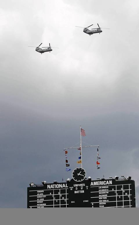 Military helicopters fly east over the Wrigley scoreboard.
