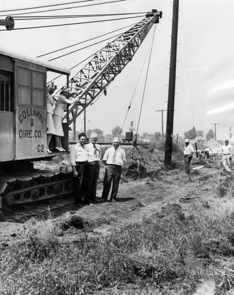 After years of planning, litigation, and general lack of action, work began on August 13, 1940 to lay tracks north of the Municipal Airport, tracks which would enable the removal of the railroad that bisected the airport. Viewing the initial work are Stewardesses Louise Mack, from left, and Phyllis Alldredge of American Airlines, a neighbor Vincent Dellacroce, the contracting engineer Charles Kulp, and assistant engineer George Amory.