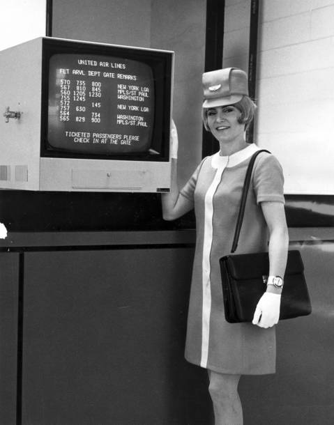 A United Air Lines hostess displays a new television flight board monitor at Midway Airport on November 7, 1968.