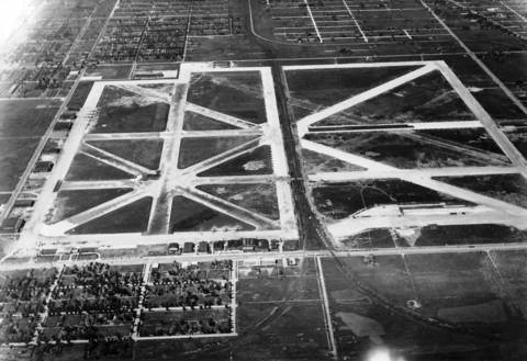 An aerial view of the Chicago Municipal Airport shows the old and new field bisected by railroad tracks. A passenger aboard a TWA Skyclub plane noticed a snail-like image crossing the center of the field. Upon landing, he learned that it was a freight train. Bewildered, the passenger left the depot wondering whether Chicago will have one useful airport or two useless ones.