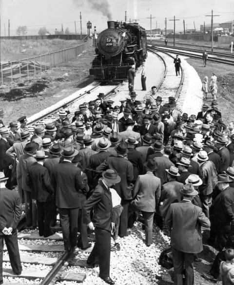 A crowd gathers around Chicago Mayor Edward Kelly (not visible) as he drives a golden spike to complete the new railroad tracks on May 1, 1941, which made it possible for Chicago Municipal Airport to expand.