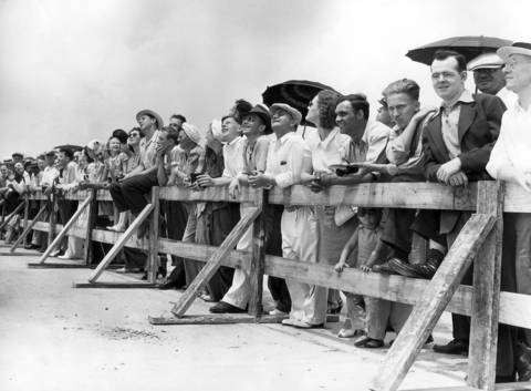 """Railbirds"" watch the air show during air races held at Chicago Municipal Airport in June 1941."