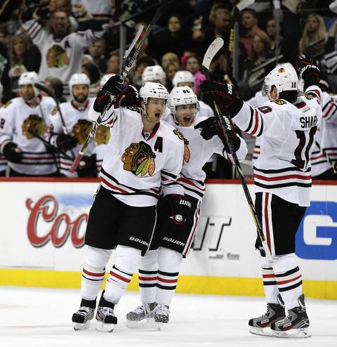 Duncan Keith celebrates his game-tying goal with Patrick Kane and Patrick Sharp in the third period in Game 3 against the Wild.