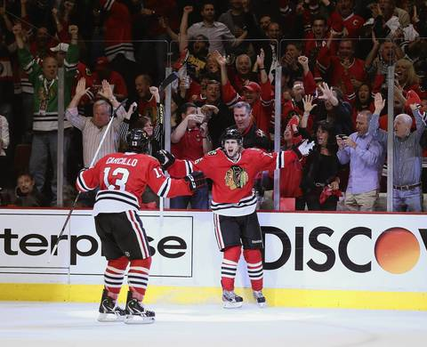 Fans cheer as Marcus Kruger celebrates his third period goal with Daniel Carcillo against the Red Wings in Game 1.