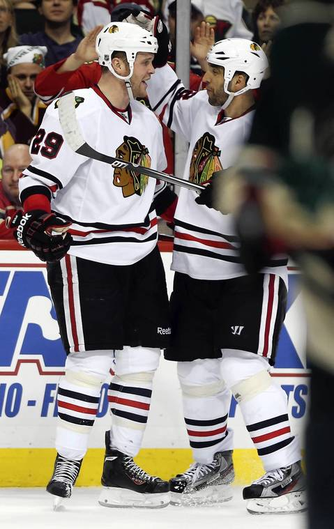 Bryan Bickell celebrates his third period goal with Michal Rozsival during a 3-0 win over the Wild in Game 4.