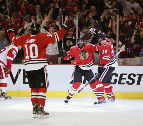 Patrick Sharp, Johnny Oduya and Michal Rozsival celebrate Oduya's third period goal against the Red Wings in Game 1.