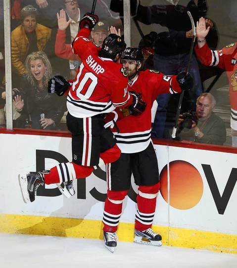 Patrick Sharp jumps into the arms of Michal Handzus after Handzus scored against the Kings in the second period.