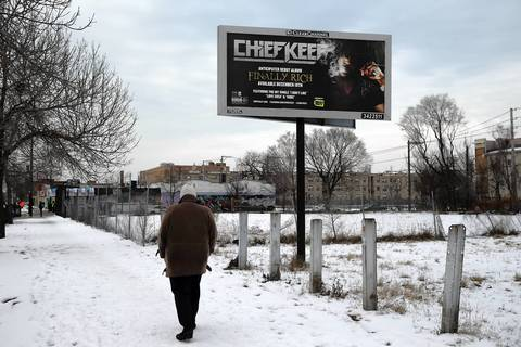 A woman walks down Cottage Grove, past a Chief Keef billboard in the Kenwood neighborhood of Chicago.