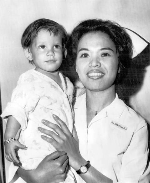 A boy found abandoned in Newark, N.J., is held by a nurse. Given the name Scott McKinley by the State Child Service, he was adopted by Chester and Dora Fronczak of Chicago who believe he is their son kidnapped two years ago.