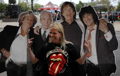 Katja Hasu of St. Louis, Mo. poses beside a cardboard cutout of the Rollings Stones outside the United Center in Chicago prior to the concert by the legendary rock and roll band.