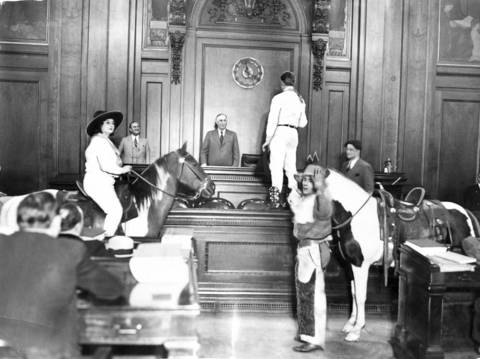 """Frankie Gibson, left, Mayor William """"Big Bill"""" Thompson, center, and Buck Spencer, right, put on a show for alderman in the legislative hall in Chicago as a Native American holds Spencer's horse in 1931."""