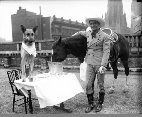 """Movie stars """"Flash,"""" a dog, eats dinner with """"Tony,"""" a horse, and Western film actor Tom Mix on April 26, 1929. Mix was the first Western megastar and helped define the genre. He made 291 films between 1909-35, and all but nine were silent films."""