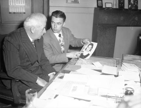 Captain Dan Gilbert, left, and El Rando Tavern bartender William Millay, 24, identify a picture of murder victim Roberta Rinearson in December 1948, days after her body was found. Police tried for years to find Roberta's killer, including following a lead that she had dinner with a soft-voiced man at a bar the night she disappeared.