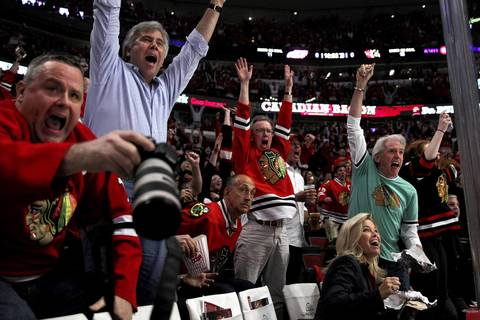 Blackhawks fans celebrate as Patrick Sharp scores a first period goal against the Detroit Red Wings in Game 7 semifinals at the United Center.