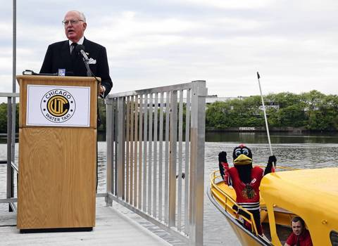 Blackhawks mascot Tommy Blackhawk photo bombs Ald. Ed Burke's speech on the start of Chicago Water Taxi rush hour service.