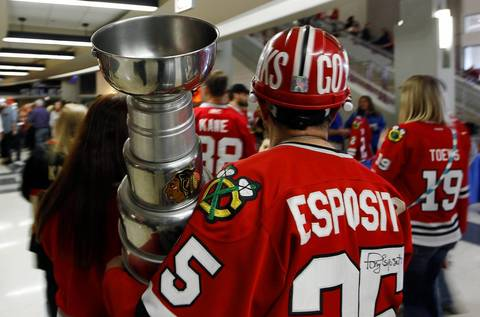 A Blackhawks fan carries a replica Stanley Cup before Game 5 of the Hawks-Kings Western Conference Finals in the Stanley Cup Playoffs at the United Center.