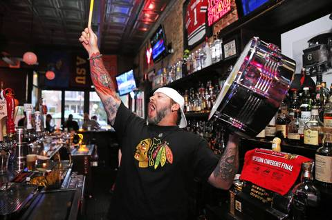 Blackhawks fan and bartender Rick Moschel, fires up the crowd before the start of Game 3 of the Hawks-Kings Western Conference Finals at Third Rail Tavern in Chicago.