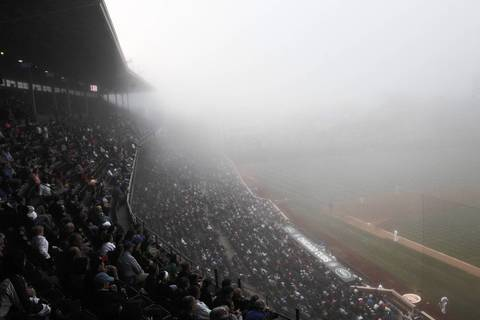 Fog at Wrigley Field makes it hard for spectators to look down the third base line during the second inning between the Chicago Cubs and the Cincinnati Reds.