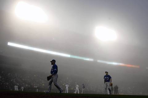 Toronto Blue Jays' Edwin Encarnacion leaves the playing field during fog delay in the third inning against the Chicago White Sox at U.S. Cellular Field in Chicago.