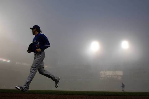 Toronto Blue Jays' Colby Rasmus leaves the playing field during fog delay in the third inning against the Chicago White Sox during at U.S. Cellular Field.