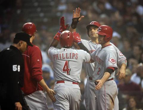 Cincinnati Reds second baseman Brandon Phillips (4) gets high fives at home from teammates after his grand slam against the Chicago Cubs, during the third inning of their game at Wrigley Field.