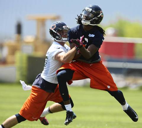 Devin Aromashodu (right) and safety Chris Conte collide.