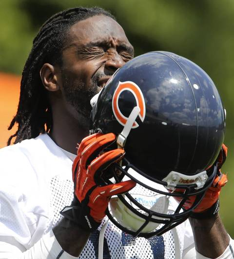 Cornerback Charles Tillman prepares to put on his helmet after wiping away some sweat.