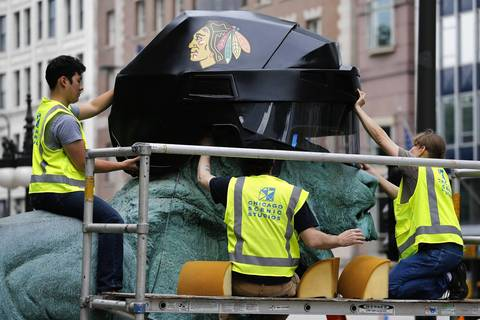 Workers place giant custom made Chicago Blackhawks helmets on the Art Institute lions for the Stanley Cup Final.
