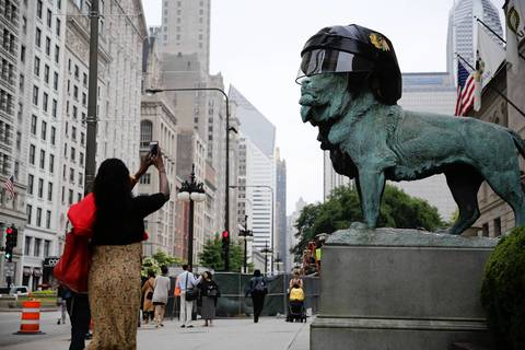 A pedestrian stops to photograph the Art Institute lions that are wearing custom-made Chicago Blackhawks helmets for the Stanley Cup Final.