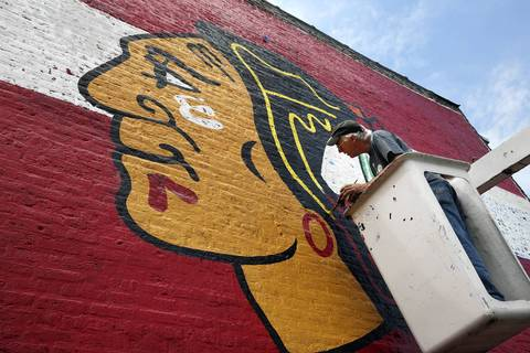 Sign painter Ches Perry of Right Way Signs paints a giant Chicago Blackhawks mural on a wall around 4200 N. Milwaukee Avenue.