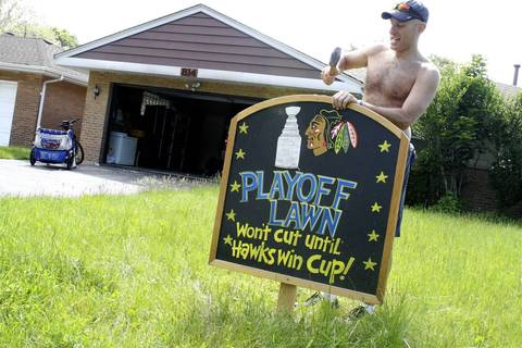 Frank Miller, 44, hammers a sign in the front yard of his Park Ridge home. Despite a bill from the city for having to cut his grass, Miller said he won't break out his lawnmower until the Blackhawks win the Stanley Cup.