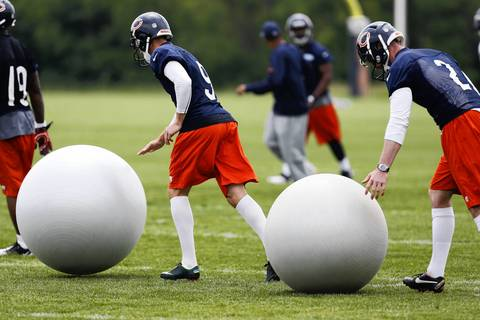 Bears kickers Robbie Gould and Austin Signor (2) roll two large balls on the field.