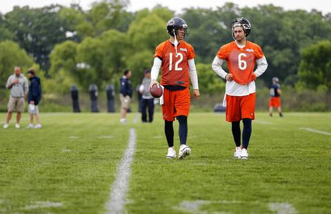 Quarterbacks Josh McCown (12) and Jay Cutler walk off the field.