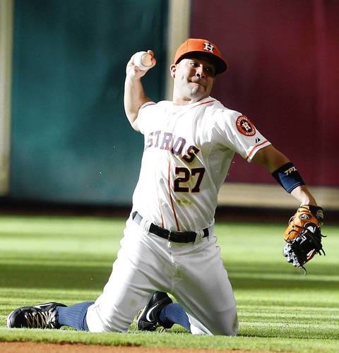 the Astros' Jose Altuve throws from his knees after making a diving stop on a ball hit by Alexei Ramirez in the first inning.