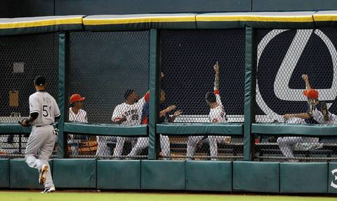 Astros players in the bullpen point to a home run hit by Chris Carter as Alex Rios looks on.