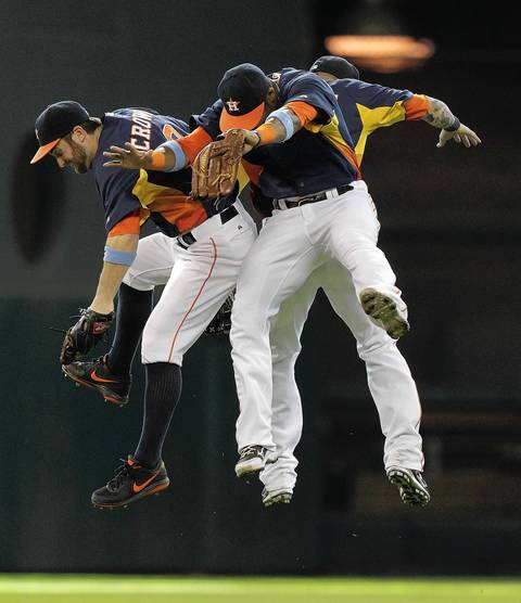 The Astros' Trevor Crowe, Brandon Barnes and Jimmy Paredes celebrate after the final out.