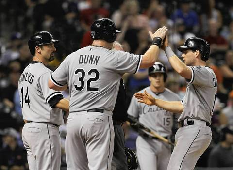 Adam Dunn high fives Conor Gillaspie and Paul Konerko after they scored on a triple by Dayan Viciedo.