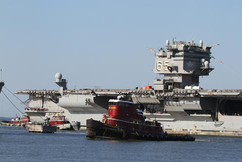Tugboats guide the USS Enterprise into Newport News Shipyard for the final time.
