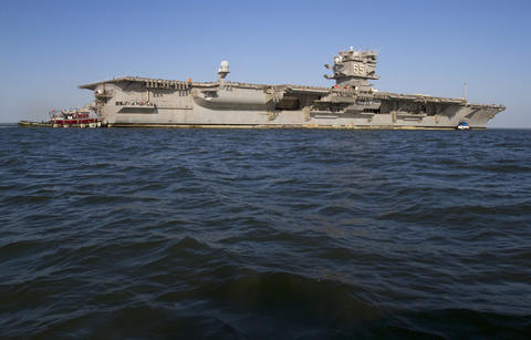 The USS Enterprise is towed from Naval Station Norfolk to the Newport News shipyard on Thursday.