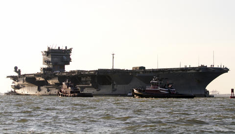 Tugboats move to assist towing the USS Enterprise from Naval Station Norfolk to the Newport News shipyard on Thursday.
