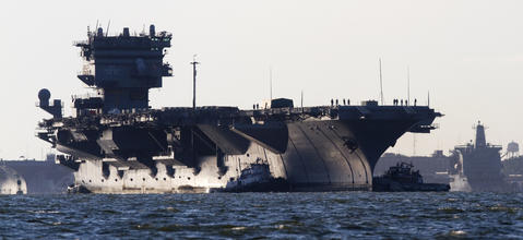 The USS Enterprise is towed out of Naval Station Norfolk on its way to the Newport News shipyard on Thursday.