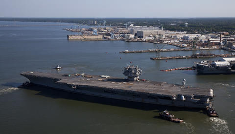 The USS Enterprise is towed to the Newport News Shipyard on Thursday.