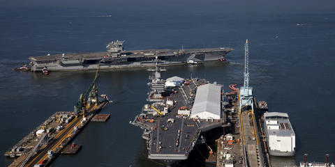 The USS Enterprise is towed past the USS Roosevelt as it arrives at the Newport News Shipyard on Thursday morning.