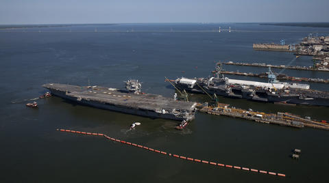 The USS Enterprise is towed towards the pier at Newport News Shipyard on Thursday.