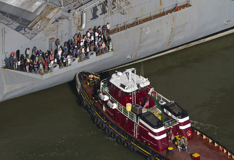 People stand on a deck of the USS Enterprise as the aircraft carrier is towed to Newport News Shipyard on Thursday.