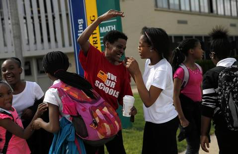 """Ericson Elementary Scholastic Academy volunteer Michelle Rose, center, hugs some of the students while chanting """"we saved our school"""" after receiving news that their school will not be closed. Rose has three grandchildren at Ericson."""