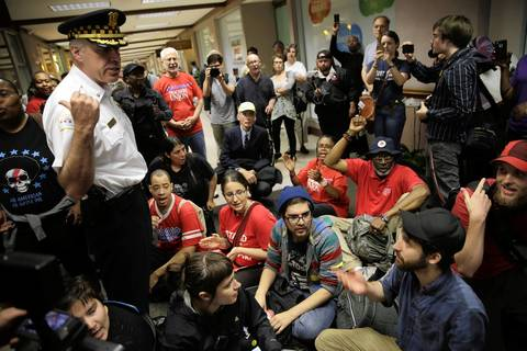 Chicago Police warn activists not to sit as they protest in the corridor adjacent to the CPS headquarters lobby.