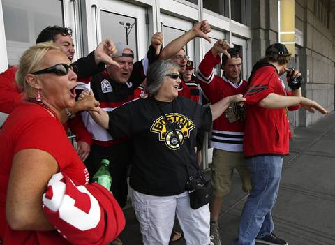 Bruins fan Julie Trono of Dedham, Mass., tries to gather Blackhawks fans for a picture before Game 5 of the Stanley Cup Final at the United Center.