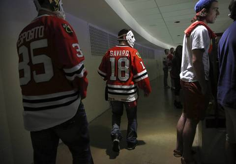 Sean Duplessis, of Calgary, center, wears a vintage goalie mask while walking to his seat in the second period of Game 5 of the Stanley Cup Final at the United Center.