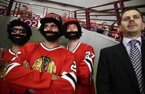 Three men sporting faux playoff beards wait for a break in play to get to their seats in the second period of Game 5 of the Stanley Cup Final at the United Center.